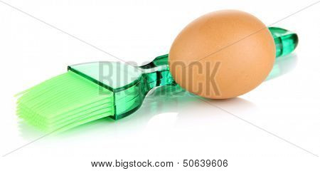 Brown egg and pastry brush isolated on white