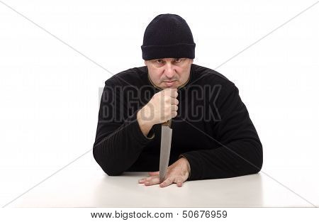 Murderer in black clothes threatening with big knife