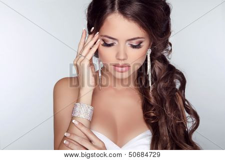 Beautiful Woman With Curly Hair And Evening Make-up Isolated On Grey Background. Jewelry And Beauty.