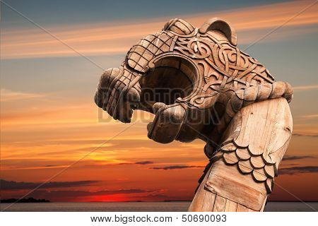 Carved Wooden Dragon On The Bow Of Viking Ship Above Evening Cloudy Sky