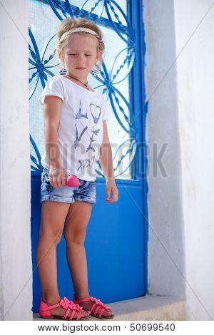Adorable Little Girl Standing Near Blue Door Of Old House In Emporio Village, Santorini, Greece