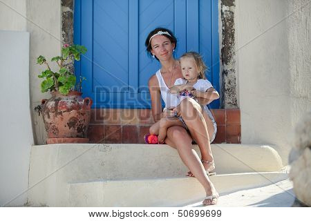 Young Mother And Her Daughter Sitting On Doorstep Of Old House In Emporio Village, Santorini, Greece