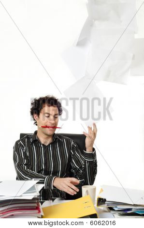 Man Sitting At Desk Throwing Up Paperwork