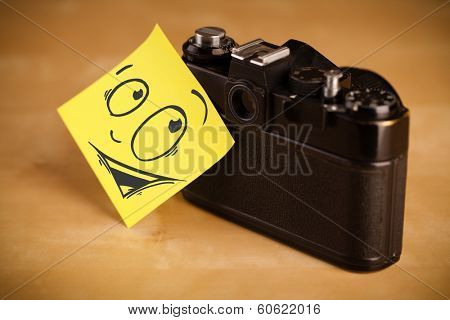 Drawn smiley face on a  note stuck on photo camera