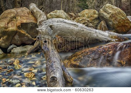 Ice hangs on a log in the sprigtime in the Wasatch National Forest in Utah USA shot in slow exposure. poster