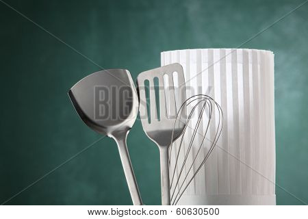 kitchen utensil and the chef's hat in front of the chalkboard