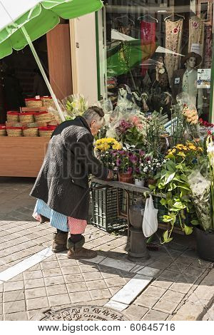 Old Woman Attending His Itinerant Position Of Flowers In The Carcel Baja Street, Granada, Spain