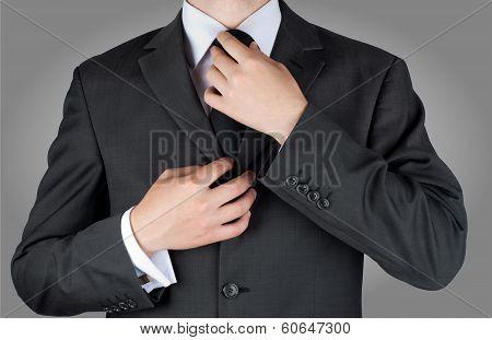 businessman in black costume tie one's necktie