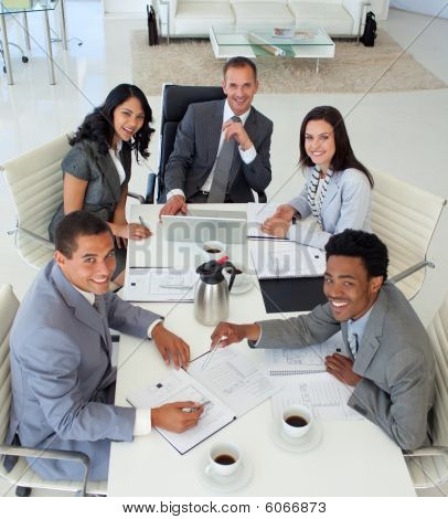 Multi-ethnic smiling business people working in a meeting poster