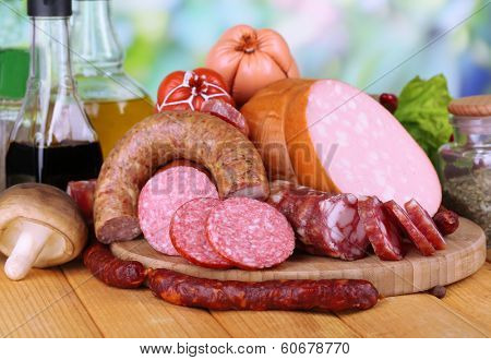 Different sausages on wooden table on natural background poster