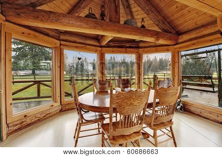 Bright dining room in log cabin house with floor-to-ceiling windows rustic dining table set and cathedral ceiling with beams.
