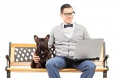 Young man sitting on a bench with his dog and working on laptop isolated on white background poster