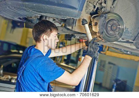 garage auto mechanic repairman checking car brake during automobile maintenance at repair service station