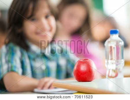 Happy little boy with apple and water bottle sitting in classrom and smiling