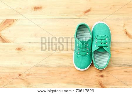 Green  Shoes On Wooden Floor.