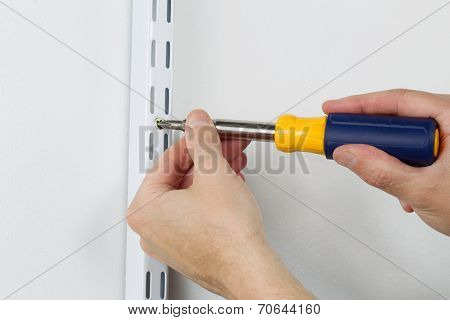Installing Metal Bracket On Wall With Hand Screwdriver