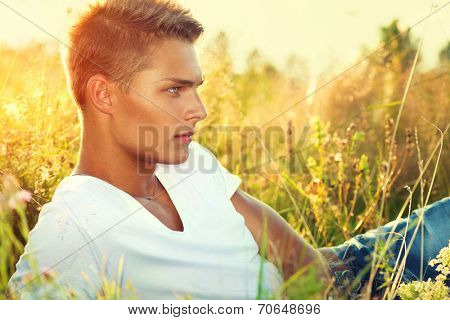 Handsome guy lying on the field. Young man enjoying nature outdoors.