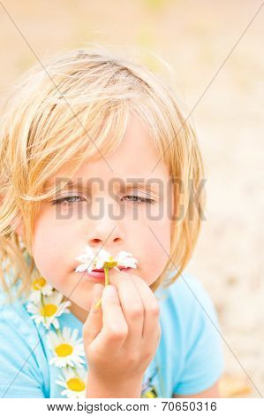 Goofy Little Blond Girl Smelling A Daisy
