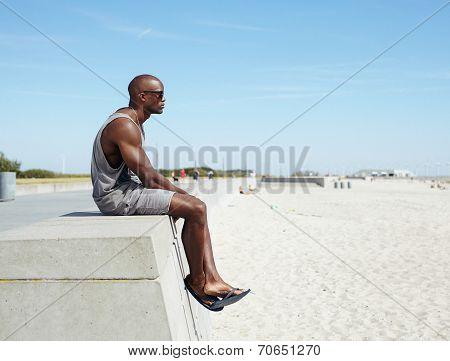 African Man Sitting On A Beach Promenade