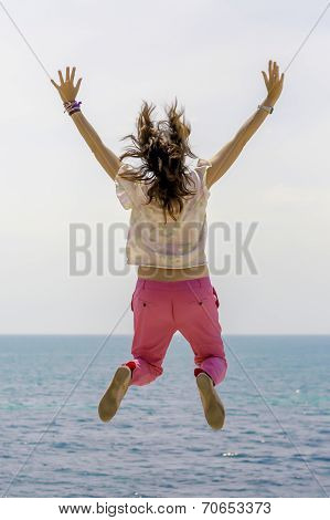 Young Woman Jumping By The Sea