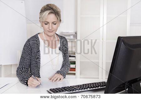 Senior Businesswoman Sitting At Desk Writing Something.