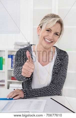 Smiling Older Businesswoman Sitting At Desk With Thumbs Up.