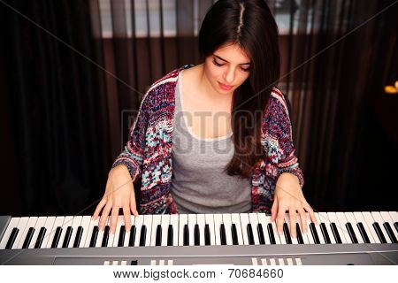 Young beautiful woman playing on piano at home