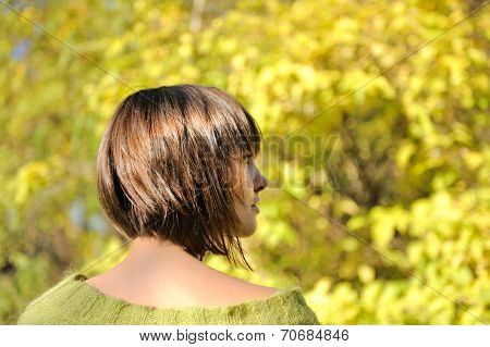Beautiful young woman wearing short bob hairstyle autumn outdoor, focus on a hair.