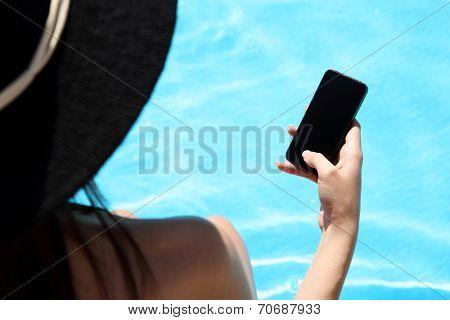 Closeup image of female hand using smartphone