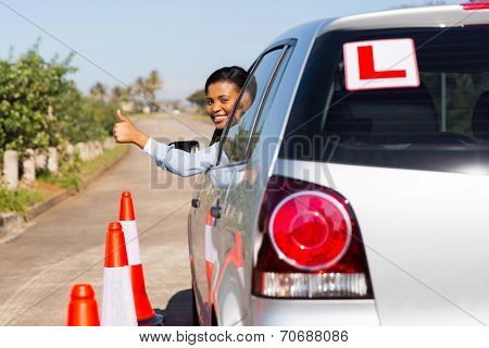 beautiful african learner driver looking out of the car window and giving thumb up