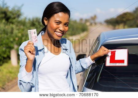 african woman removing learner driver sign after getting her driving license