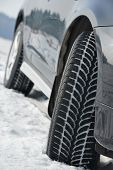 Car with winter tyres installed on light alloy wheels in snowy outdoors road poster