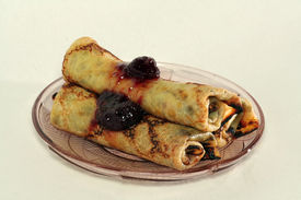 Rolled Pancakes With Strawberry Jam On A Glass Plate