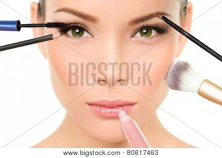 Makeup concept - Asian woman with many brushes against beauty face putting mascara, blush and lip gloss