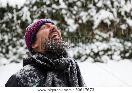Man With Outstreched Tongue Is Catching Snowflakes