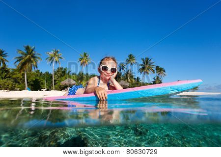 Adorable little girl on tropical vacation swimming in ocean