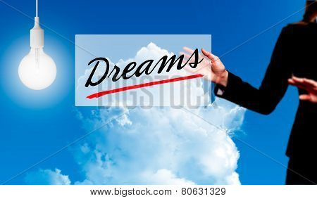 Business woman holding dreams sign - business concept