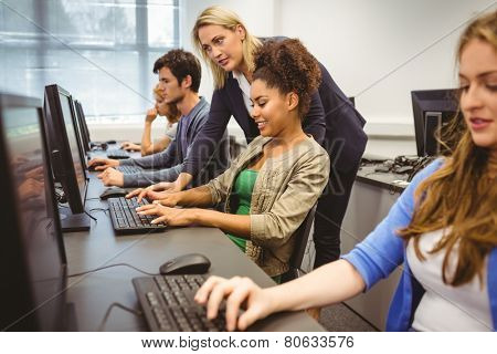 Attractive teacher helping her student in computer class at the university poster