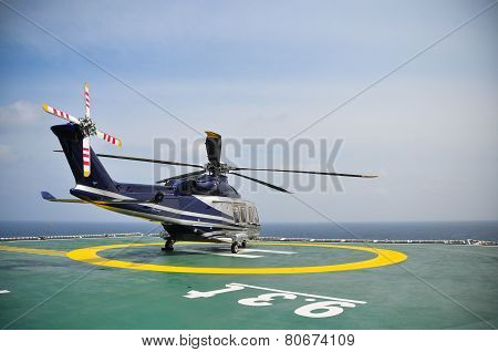Helicopter parking on helideck and waiting passenger. Helicopter landing and waiting for ground serv
