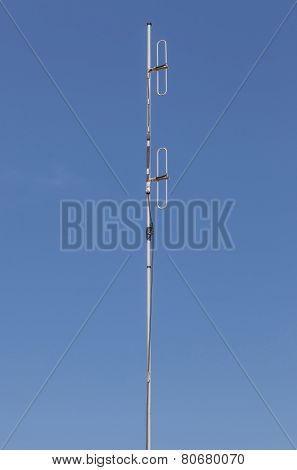 Looking Up The Telecommunication Dipole Antenna With Blue Sky Background.