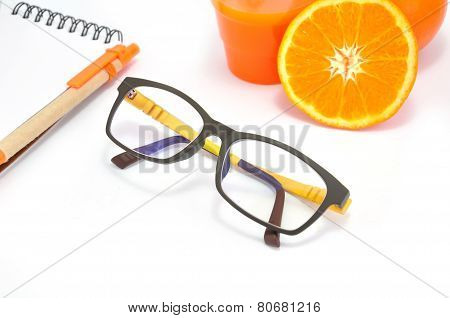 Modern Glasses And Notepad Nearing A Group Of Orange