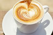 Cappuchino or latte coffe in a white cup  with heart shaped foam on wooden board poster