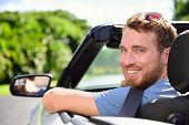 Car driver - young man wearing safety belt driving convertible on road trip in summer. Caucasian male looking at camera. poster