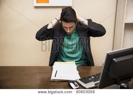 Preoccupied, worried young man staring at computer in office