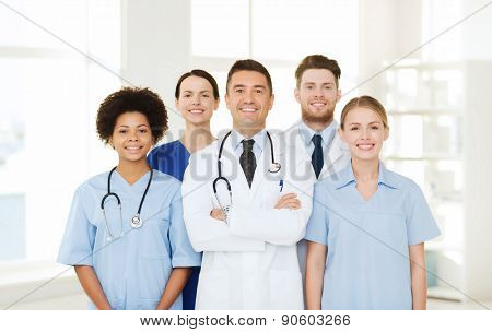 hospital, profession, people and medicine concept - group of happy doctors at hospital poster