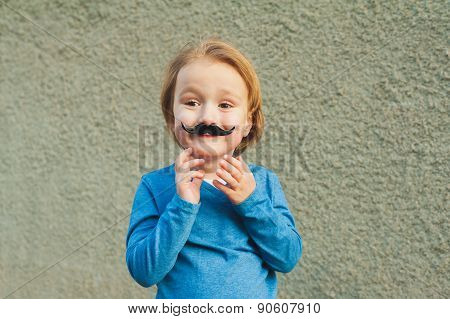 Outdoor close up portrait of a cute little boy with fake italian mustache