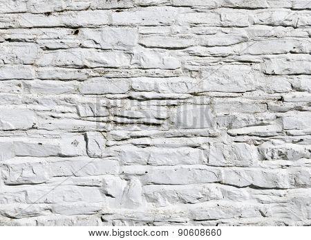 Whitewashed paint on stone wall close up.