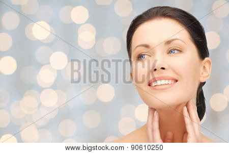 beauty, people, holidays, luxury and health concept - beautiful young woman touching her face and neck over lights background