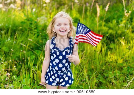 Beautiful Little Girl With Long Curly Blond Hair With American Flag In Her Hand