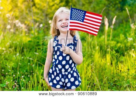 Funny Little Girl With Long Curly Blond Hair Holding An American Flag, Waving It And Laughing